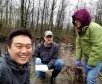 three students outside in the wetland
