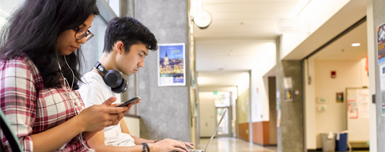 student on a phone and student on a laptop on a bench