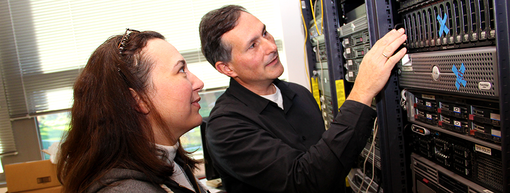 Image of student and faculty discussing the computer servers on campus